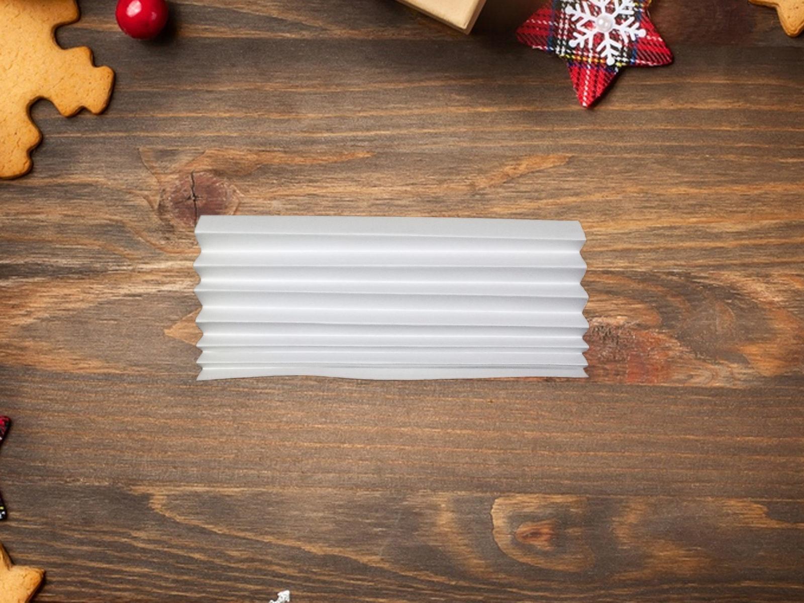 Даже при отсутствии снега за окном на Новый год особую атмосферу в доме помогут создать бумажные снежинки. Они бывают очень разными, а чтобы сделать объемную снежинку из бумаги, нужно сложить лист гармошкой, вырезать узор и расправить каждый полукруг. Материалы: • лист белой бумаги А4; • степлер; • ножницы маникюрные. Инструкции к работе Располагаем лист офисной бумаги А4 вертикально. Складываем его гармошкой. Общая ширина чуть больше 1 см. Фото 3. Теперь необходимо сложить нашу заготовку ровно пополам. Так мы наметим середину. В этом месте скрепляем гармошку степлером. Скрепка должна быть расположена поперек бумажной полоски. Фото 4. При помощи ножниц вырезаем с двух сторон на заготовке узор. Фото 5. Расправляем бумагу. Соединяем концы заготовки до образования круга. Концы скрепляем между собой степлером. Фото 6. Такую снежинку можно сделать еще больше. Для этого просто делаем вторую заготовку (аналогичную первой). Затем их необходимо расправить до формы полукруга, а затем скрепить вместе. А если взять цветную бумагу, например, голубую, получатся красивые разноцветные снежинки. Ими можно просто, но эффектно, декорировать как елку, так и офис или квартиру -2