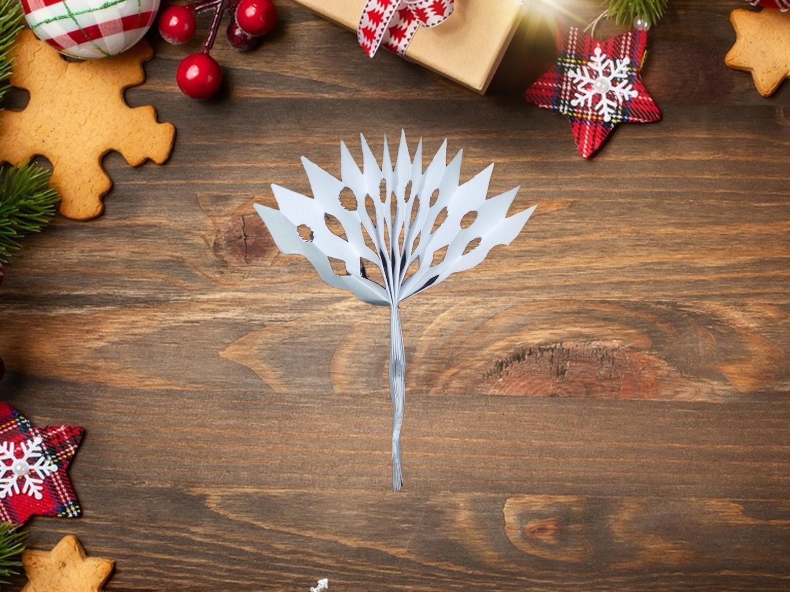 Даже при отсутствии снега за окном на Новый год особую атмосферу в доме помогут создать бумажные снежинки. Они бывают очень разными, а чтобы сделать объемную снежинку из бумаги, нужно сложить лист гармошкой, вырезать узор и расправить каждый полукруг. Материалы: • лист белой бумаги А4; • степлер; • ножницы маникюрные. Инструкции к работе Располагаем лист офисной бумаги А4 вертикально. Складываем его гармошкой. Общая ширина чуть больше 1 см. Фото 3. Теперь необходимо сложить нашу заготовку ровно пополам. Так мы наметим середину. В этом месте скрепляем гармошку степлером. Скрепка должна быть расположена поперек бумажной полоски. Фото 4. При помощи ножниц вырезаем с двух сторон на заготовке узор. Фото 5. Расправляем бумагу. Соединяем концы заготовки до образования круга. Концы скрепляем между собой степлером. Фото 6. Такую снежинку можно сделать еще больше. Для этого просто делаем вторую заготовку (аналогичную первой). Затем их необходимо расправить до формы полукруга, а затем скрепить вместе. А если взять цветную бумагу, например, голубую, получатся красивые разноцветные снежинки. Ими можно просто, но эффектно, декорировать как елку, так и офис или квартиру -5